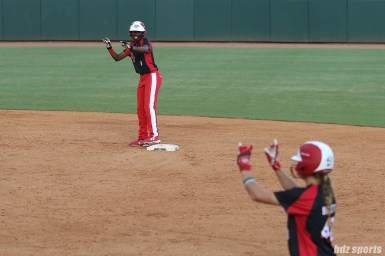 """Scrap Yard Dawgs Kayla Winkfield (9) and Allexis Bennett (43) give the """"Dawgs"""" sign after advancing to second and first base"""