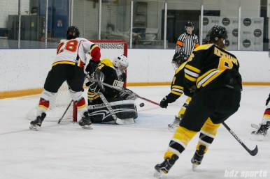 Boston Blades goalie Jetta Rackleff (21) stops Calgary Inferno forward Louise Warren's (28) shot on goal