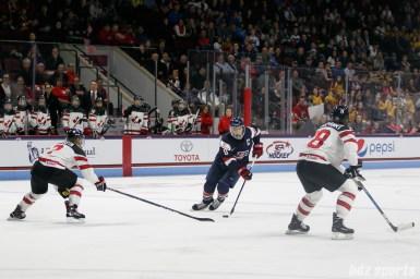 Team USA forward Meghan Duggan (10) controls the puck for Team USA