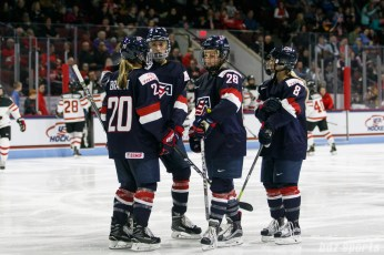Team USA players Hannah Brandt (20), Megan Keller (5), Amanda Kessel (28), and Emily Pfalzer (8) gather before play restarts