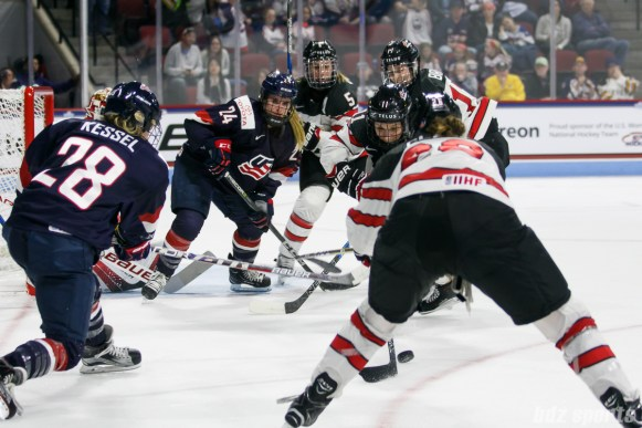The puck is loose in front of Team USA and Team Canada players