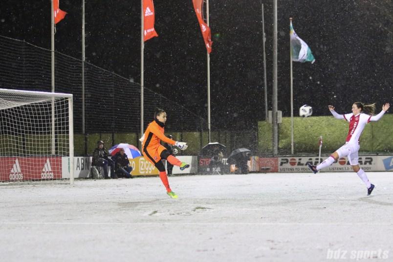 FC Twente goalie Nicky Evrard (1) clears the ball past oncoming Ajax forward Marjolijn van den Bighelaar (11)
