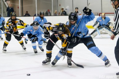 Boston Pride forward Jillian Dempsey (14) attempts to shield off Buffalo Beauts forward Rebecca Vint (12) from the puck