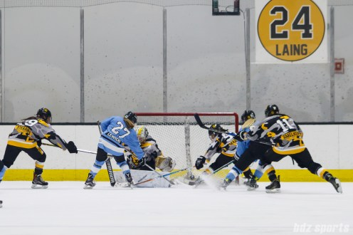 The puck pops loose in front of the net but the Boston Pride manage to keep it out
