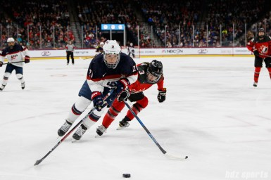 Team USA forward Hilary Knight (21) controls the puck while being defended by Team Canada defender Jocelyne Larocque (3)
