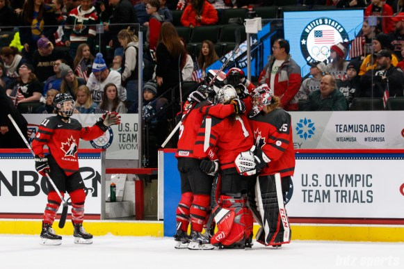 Team Canada players hug goalie Shannon Szabados (1) after Team Canada defeated Team USA in overtime