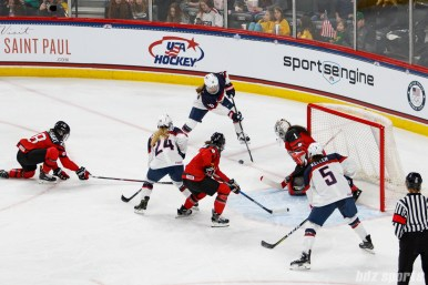 Team USA forward Hannah Brandt (20) plays the puck in front of Team Canada goalie Shannon Szabados (1)