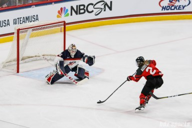 Team Canada forward Meghan Agosta (2) takes a shot on Team USA goalie Maddie Rooney (35)