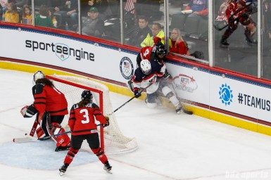 Team USA forward Jocelyne Lamoureux-Davidson (17) and Team Canada defender Bridgette Lacquette (4) crash in the boards while trying to gain possession of the puck