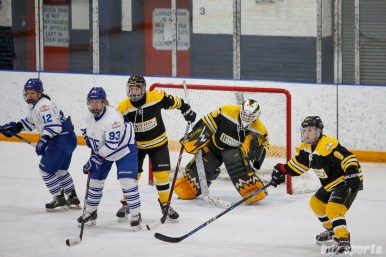 Boston Blades goalie Lauren Dahm (35) looks around teammate defender Dru Burns (7) to keep an eye on the puck
