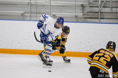 Toronto Furies defender Jessica Platt (11) works to shield the puck from Boston Blades forward Casey Stathopoulos (12)