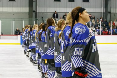 Team NWHL stand for the playing of the national anthem