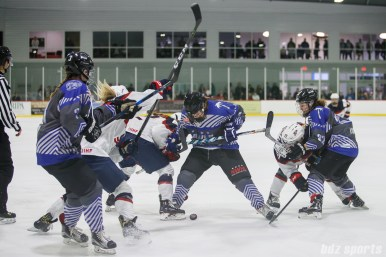 Team NWHL and Team USA players battle for the puck after a faceoff