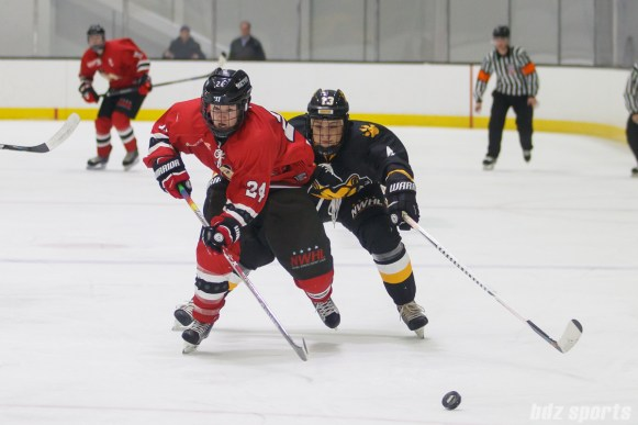 Metropolitan Riveters forward Harrison Browne (24) chases down the puck while being pressured by Boston Pride forward Kaleigh Fratkin (13)