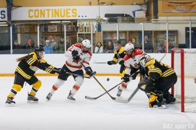 The puck pops loose in front of the Boston Blades goal