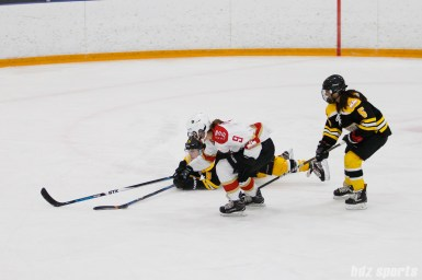 Boston Blades defender Sato Kikuchi (8) dives to takes the puck away from Kunlun Red Stars forward Alex Carpenter (9)