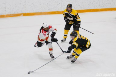 Boston Blades defender Jordan Hampton (91) strips the puck from Kunlun Red Stars forward Rachel Llanes (91)