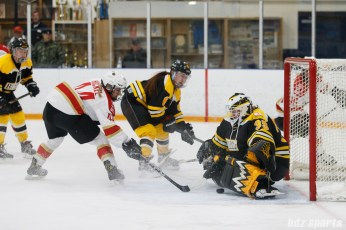 Kunlun Red Stars forward Zoe Hickel (44) looks to slip the puck past Boston Blades goalie Lauren Dahm (35)