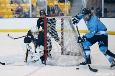 Buffalo Beauts forward Hayley Scamurra (14) brings the puck around the back of the Boston Pride goal