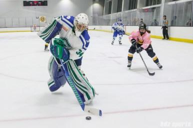 Connecticut Whale goalie Sydney Rossman (34) sends the puck around the net while Boston Pride forward Jillian Dempsey (14) applies pressure