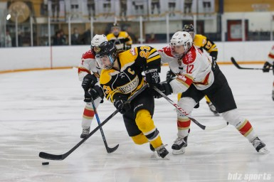 Boston Blades forward Melissa Bizzari (23) controls the puck while being defnded by Kunlun Red Star forward Stephanie Anderson (12)