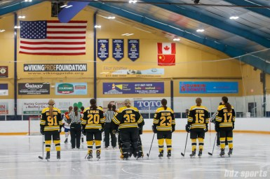 The starting line ups for the Boston Blades and Montreal Les Canadiennes stand for the playing of the national anthems