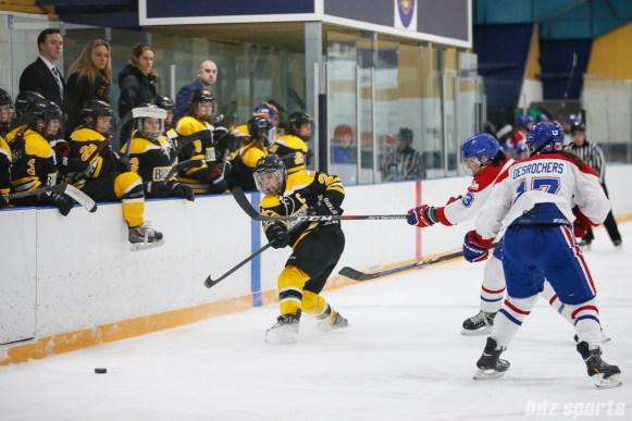 Boston Blades forward Melissa Bizzari (23) sends the puck down ice