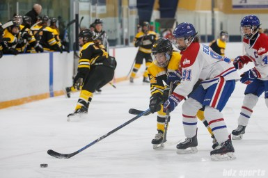 Boston Blades forward Casey Stathopoulos (12) battles Montreal Les Canadiennes defender Laurence Beaulieu (91) for the puck