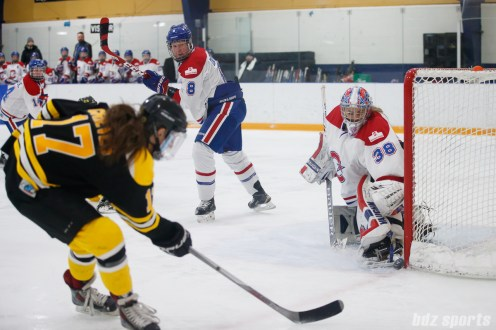 The puck hits the post as Montreal Les Canadiennes goalie Emerance Maschmeyer (38) and Boston Blades forward Meghan Grieves (17) look on