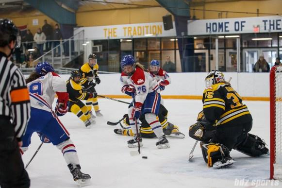 Montreal Les Canadiennes forward Karell Emard (76) looks to slip the puck past Boston Blades goalie Lauren Dahm (35)