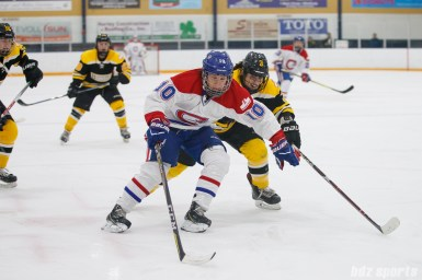 Montreal Les Canadiennes forward Noemie Marin (10) looks to control the puck while being defended by Boston Blades forward Courtney Turner (3)