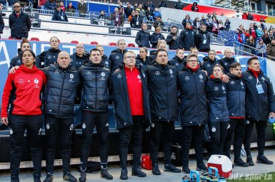 German women's national soccer team coaches and players stand for the playing of the German national anthem