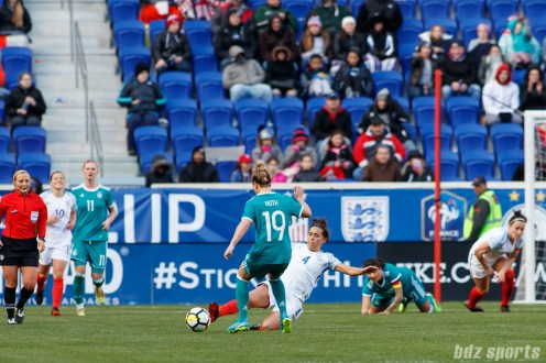 Team England midfielder Fara Williams (4) slide tackles the ball away from Team Germany forward Svenja Huth (19)