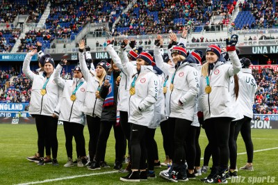 The USA women's hockey team waves to the crowd during a half time