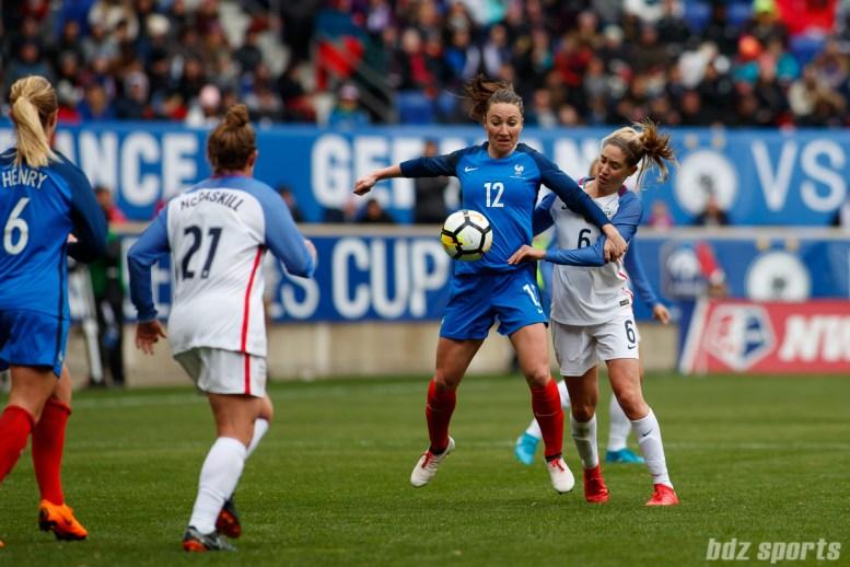 Team USA forward Lynn Williams (12) traps the all while being pressured by Team USA midfielder Morgan Brian (6)