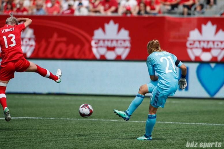 Team Germany goalie Carina Schluter (21) and Team Canada midfielder Sophie Schmidt (13)