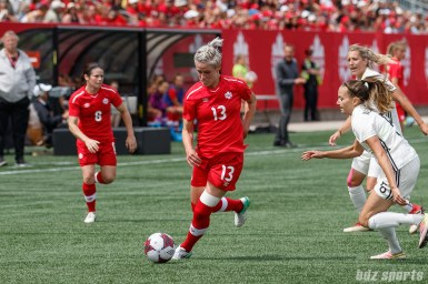 Team Canada midfielder Sophie Schmidt (13) and Team Germany midfielder Kristin Demann (6)
