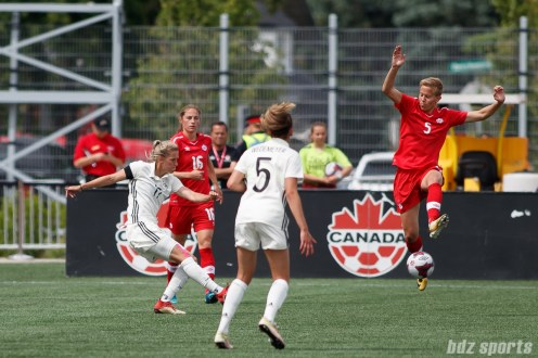 Team Canada defender Rebecca Quinn (5) looks to block a cross from Team Germany defender Verena Faisst (17)