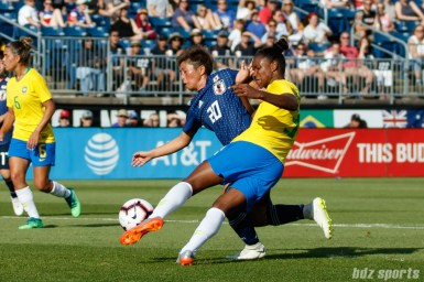 Team Brazil defender Daiane (3) and Team Japan forward Kumi Yokoyama (20)