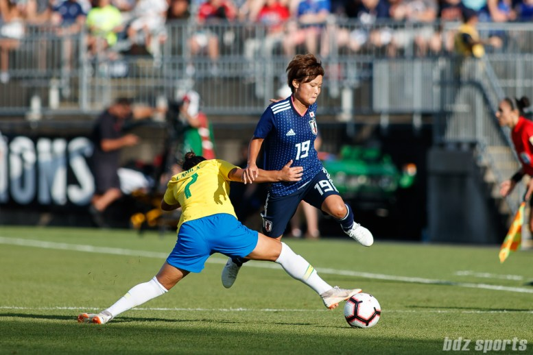 Team Japan midfielder Rika Masuya (19) and Team Brazil midfielder Camila (7)