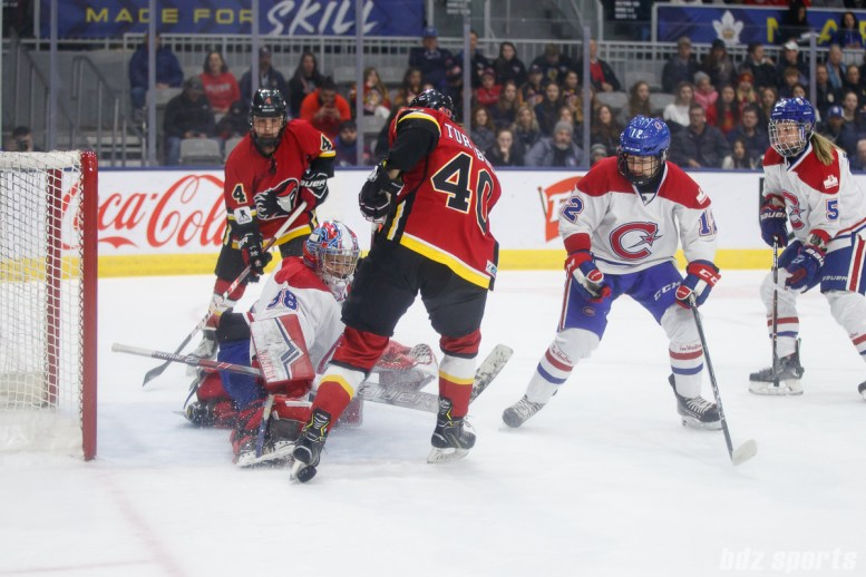 Montreal Les Canadiennes goalie Emerance Maschmeyer (38) and Calgary Inferno forward Blayre Turnbull (40)