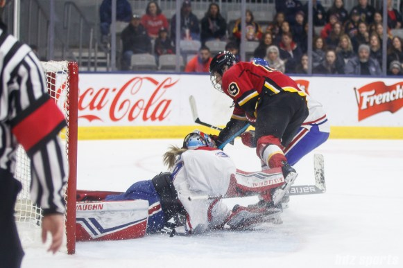 Montreal Les Canadiennes goalie Emerance Maschmeyer (38) and Calgary Inferno forward Brianne Jenner (19)