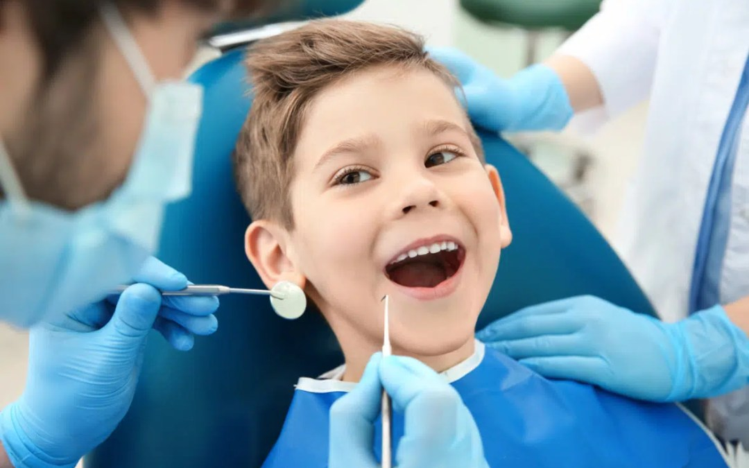 a young boy who is calm and seated at a dental chair
