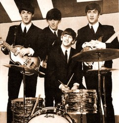 The Beatles posing around Ringo's drum kit