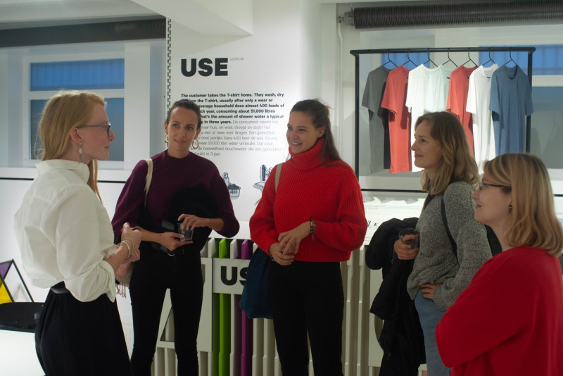 The basement of the Fashion for Good Museum displays and explains the production cycle of T-shirts. These women eagerly listen to a Fashion for Good tour guide explain the goals of the museum.
