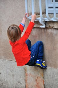 child hanging from grille