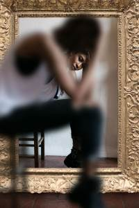 woman sitting in front of mirror