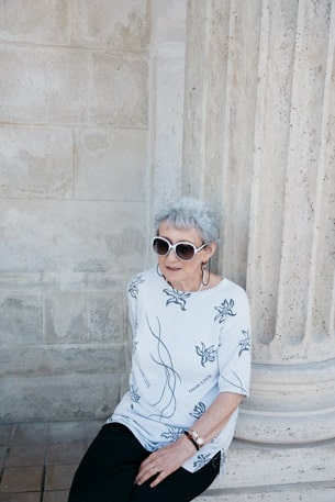 Woman sitting by a column