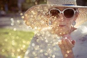 Woman blowing glitter against the sun