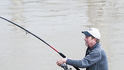 Mick reels in a paddlefish, slowly but assuredly getting it closer to shore.